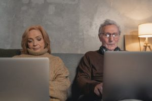 old couple with laptops engaging in facebook social media competition with a holiday home vacation rental self catering stay