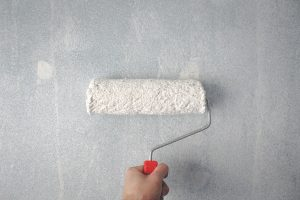 hand repainting a wall, an important component for holiday home interior design and the most common piece of maintenance for a self catering stay vaction rental